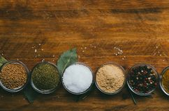 Variety of spices in round glass bowls - ground ginger, hops-suneli, kari, black pepper and mix. On a wooden table stock image