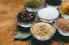 Variety of spices in round glass bowls - ground ginger, hops-suneli, kari, black pepper and mix. On a wooden table stock photos