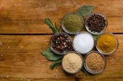 Variety of spices in round glass bowls - ground ginger, hops-suneli, kari, black pepper and a mixture. Variety of spices in round glass bowls - ground ginger stock photo