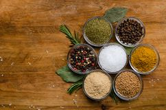 Variety of spices in round glass bowls - ground ginger, hops-suneli, kari, black pepper and a mixture. Variety of spices in round glass bowls - ground ginger stock photography