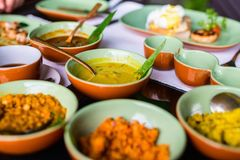 Sri Lankan food. Variety of Sri Lankan curry in bowls on table stock photo