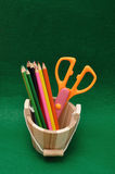 Variety of stationary in a wooden bucket. Against a colorful background Stock Images