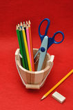 Variety of stationary in a wooden bucket. Against a colorful background Royalty Free Stock Image