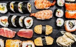 Variety of sushi: maki, nigiri,rolls on dark wooden background Royalty Free Stock Photography