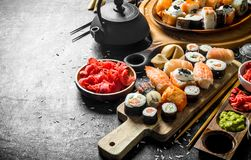 A variety of sushi, maki and rolls with ginger and soy sauce. On rustic background royalty free stock photo