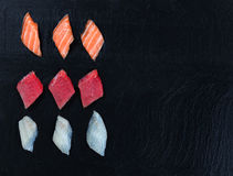 Variety of Sushi on natural slate stone background. Overhead view of fresh Japanese sushi on black slate. Horizontal layout with plenty of copy space Stock Photography