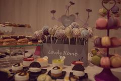 Variety of sweet treats at a candy bar. Delicious sweet assortment of macarons, bite-sized bonbons, cake pops in a square display with a banner that reads ` Stock Photography