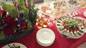 Variety of tasty snacks, canapes, alcohol and water in the cups at the banquet on catering stock video footage