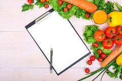 A variety of tasty vegetables. Healthful vitamins on a bright wooden background. Organic tomatoes, peppers, carrots, greens. Stock Photos