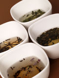A variety of teas. In white pots on a brown background Royalty Free Stock Photo