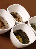 A variety of teas. In white pots on a brown background Royalty Free Stock Image