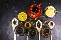 A variety of teas, spices and fruits on dark textured background royalty free stock photo