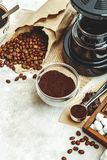 Variety things for prepare coffee. Roasted beans, ground coffee, scoop, electric coffee machine and assortment of sweets and spice royalty free stock photo