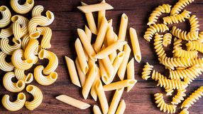 Variety of types and shapes of dry Italian pasta - fusilli, cavatappi and penne, top view. Uncooked whole wheat italian pasta. Ima stock photos