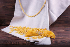 A variety of types and shapes of Italian dry pasta on a gray cloth and wooden background. Uncooked, hard, raw and dry macaroni. royalty free stock image