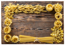 Variety of types and shapes of Italian pasta on wooden background stock image