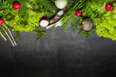 Variety of vegetables on a black wooden table. Spring still life. View from above Stock Photos