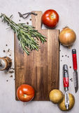Variety of vegetables, ingredients for cooking, laid out around a cutting board wooden rustic background top view close up Stock Photo