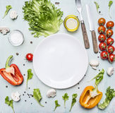 Variety of vegetables laid out around a white plate with oilknife and fork wooden rustic background top view close up. Variety of vegetables laid out around Stock Photos