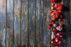 Variety of vegetables. Variety of raw organic of vegetables tomatoes, pepper, garlic, purple onion over old wooden plank background. Top view with copy space royalty free stock images