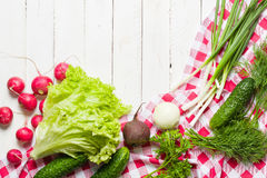 Variety of vegetables on a white wooden table together with a red checkered cloth. View from above Royalty Free Stock Images