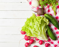 Variety of vegetables on a white wooden table together with a red checkered cloth. View from above Stock Photo