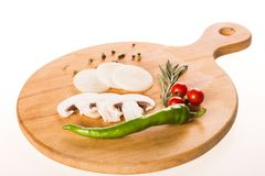 Variety of vegetables on wooden board - peppers, rosemary, tomatoes, onion and mushroom stock images