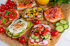 Variety of vegetarian toast sandwiches with salmon, raddish, tomatoes, cucumber, avocado,fried egg and sweet pepper Stock Photo