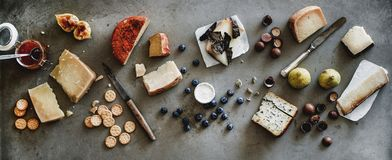Variety of wine snacks, jam and cheeses over grey background. Wine snack variety. Flat-lay of cheeses, jam, fresh fruit, nuts and crackers over rough grey