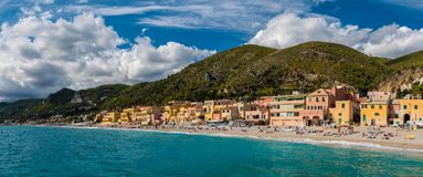 Varigotti,在萨沃纳附近的小海村庄全景,有在一个晴朗的下午期间的拥挤海滩的 库存图片
