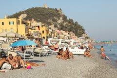 Varigotti,意大利, 2017年8月9日,拥挤海滩在意大利海岸的一个老渔夫村庄在夏时 免版税图库摄影