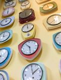 Vario degli orologi di parete d'annata che appendono contro la parete giallo-chiaro fotografia stock libera da diritti