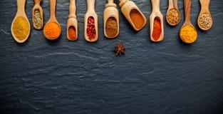Vario delle spezie e dell'erba indiane in cucchiai di legno Disposizione piana di Fotografia Stock