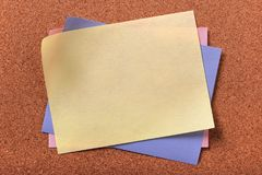 Vario fondo del bordo del sughero di colori della nota in calce appiccicosa gialla fotografie stock