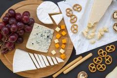 Vario formaggio sul piatto rotondo del bordo di legno con i frutti, le noci, le ciambelline salate ed i grissini su fondo scuro D fotografia stock
