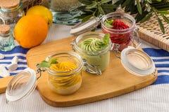 Vario sapore del gelato nell'arancia del pistacchio della fragola dei barattoli sul bordo di legno immagini stock