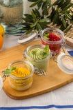 Vario sapore del gelato nell'arancia del pistacchio della fragola dei barattoli sul bordo di legno fotografia stock libera da diritti