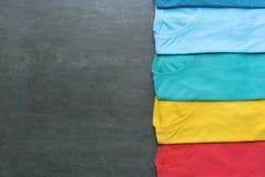 Variopinto dei vestiti della maglietta su fondo nero Immagini Stock Libere da Diritti