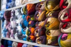Variopinto della lana delle palle del filato in un negozio del tessuto Fotografie Stock