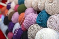 Variopinto della lana delle palle del filato in un negozio del tessuto Immagine Stock