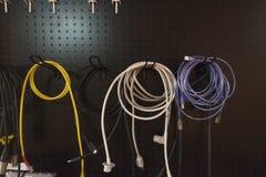 Variopinto di cavo elettrico che appende sullo scaffale di stoccaggio su backg nero immagini stock libere da diritti