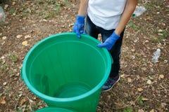 Variopinto ricicli il recipiente con le mani del ` s del bambino nei guanti blu del lattice Fuori della foto, terra sui precedent Fotografie Stock