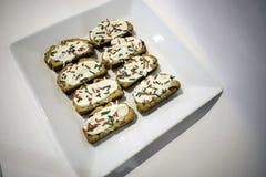 Varios adornaron las galletas en una placa blanca cuadrada Foto de archivo