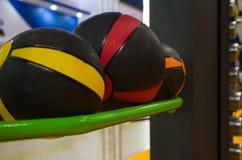 Varios baloncestos coloreados que mienten en el estante en el gimnasio para los entrenamientos imagen de archivo libre de regalías