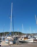 Varios barcos atados para arriba en puerto deportivo con el cielo azul fotografía de archivo