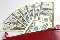 Varios billetes de dólar en un monedero rojo Foto de archivo libre de regalías