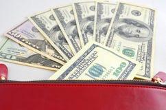 Varios billetes de dólar en un monedero rojo Fotos de archivo libres de regalías