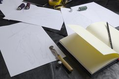 Varios bosquejos durante el trabajo del diseñador sobre la tabla Herramientas para crear la colección de la ropa fotos de archivo libres de regalías
