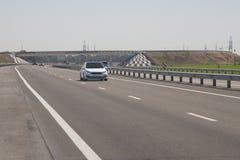 Varios coches están conduciendo a lo largo de la carretera En el fondo, el puente fotos de archivo