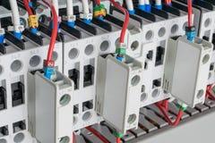 Varios contactores arreglaron en fila en un armario eléctrico Fotos de archivo